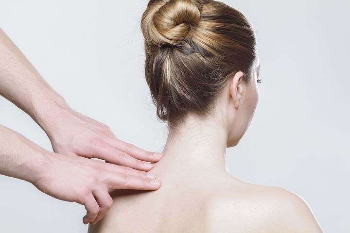 woman's back getting checked by a chiropractor