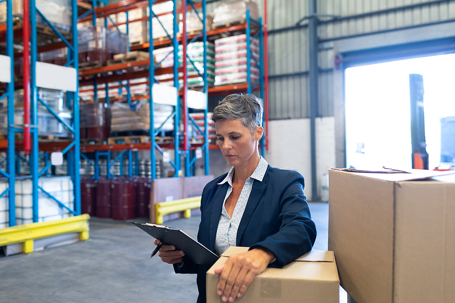 Female manager checking stocks on clipboard in a transportation and distribution warehouse.