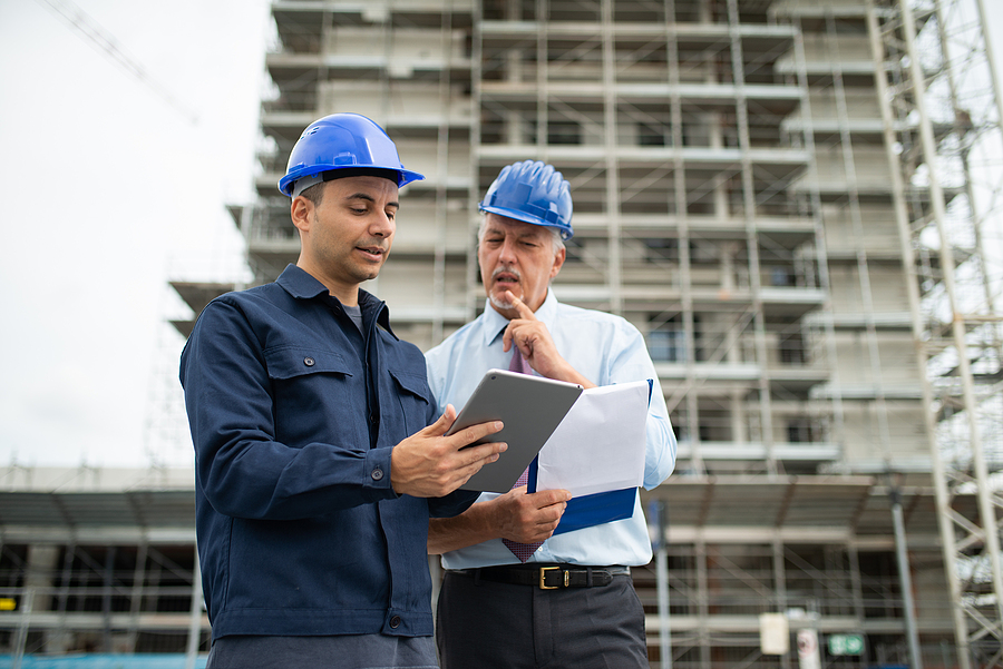 Architect with a site manager and scaffold units surrounding a construction building